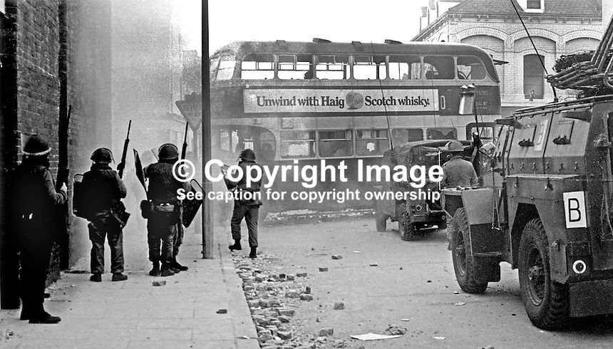British soldiers shelter behind a hijacked doubledecker bus on the loyalist Shankill Road, Belfast, N Ireland, following an outbreak of violence which was triggered by Protestant supporters of Linfield FC, attacking the predominently Roman Catholic Unity Flats on their way home from a match on Saturday 26th September 1970. The disturbances continued into the third day. 197009260349b<br /> <br /> Copyright Image from Victor Patterson, 54 Dorchester Park, Belfast, UK, BT9 6RJ<br /> <br /> t: +44 28 9066 1296<br /> m: +44 7802 353836<br /> <br /> e1: victorpatterson@me.com<br /> e2: victorpatterson@gmail.com<br /> <br /> www.victorpatterson.com<br /> <br /> IMPORTANT: Please see my Terms and Conditions of Use at www.victorpatterson.com