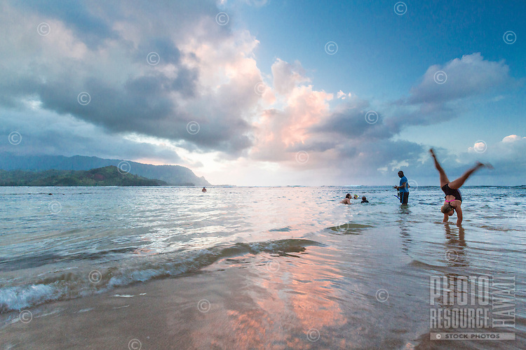 At sunset, a family swims at Hanalei Bay near Princeville Resort, Kaua'i.