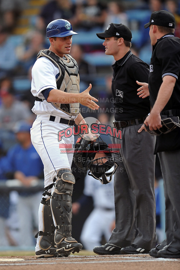 Asheville Tourists catcher Tom Murphy #9 greets umpires Blake Carnahan and Ben Levin before a game between the Lexington Legends and the Asheville Tourists at McCormick Field on April 23, 2013 in Asheville, North Carolina. The Tourists won the game 4-3. (Tony Farlow/Four Seam Images).
