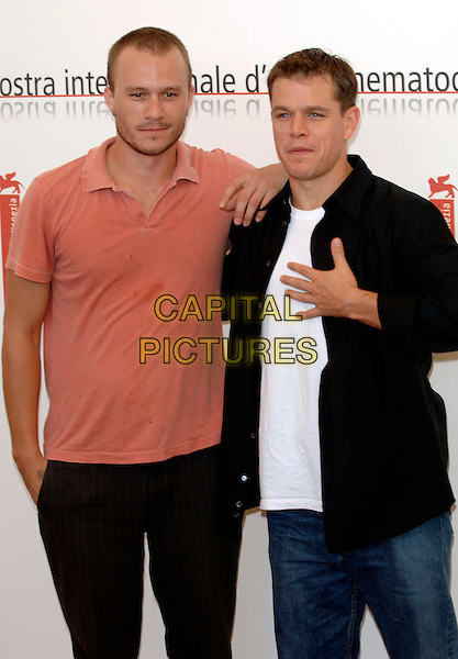 "MATT DAMON & HEATH LEDGER.photocall for ""The Bothers Grimm"".62nd International Film Festival,.Venice, 4th September 2005.half length La Biennale black shirt white t-shirt pink salmon polo hand chest.Ref: PL.www.capitalpictures.com.sales@capitalpictures.com.©Capital Pictures."