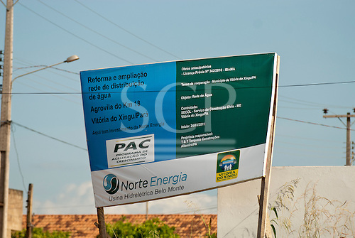 Altamira, Para State, Brazil. Agrovila do km 18. Norte Energia sign announcing the installation of a new water distribution system. Like the work, the sign is abandoned and falling down.