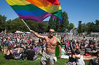 Man waving rainbow colored flag, Seattle PrideFest 2016, Pride Festival, Washington, USA.