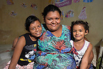 Andrea Cordoro poses with her daughters Ana Paula (left) 11, and Deborah, 5, in their small room in a building in Manaus, Brazil. The Kokama indigenous family migrated to the city in 2018, but unable to find decent housing they could afford, they joined with other poor families to take over an unoccupied building--the Casa do Estudante--in the city center. Caritas, a ministry of the Catholic Church, has helped the families in their struggle.<br /> <br /> Written parental consent obtained.