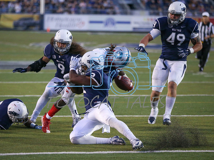 Nevada's Asauni Rufus causes New Mexico's Dameon Gamblin to fumble at the goal line during the second half at an NCAA college football game in Reno, Nev., on Saturday, Oct. 10, 2015. From left, Nevada's Dameon Baber, Matthew Lyons and Jordan Dobrich were also in on the play. (AP Photo/Cathleen Allison)