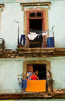 Havana Cuba Habana woman hanging laundry from porch in old worn and colorful apartment buildings in downtown city