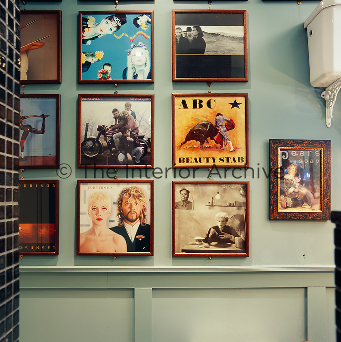 A series of framed contemporary record album covers are displayed on a wall painted in eau de nil.