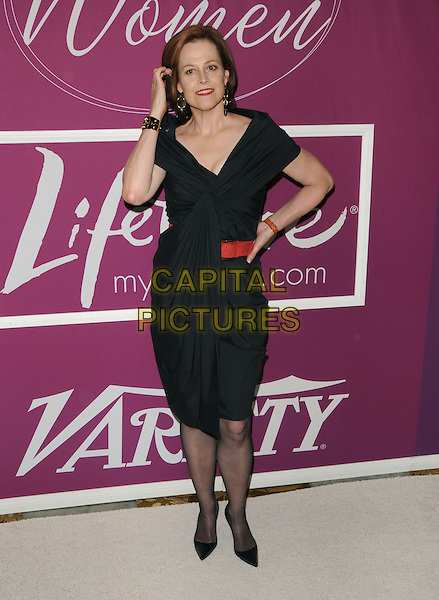 SIGOURNEY WEAVER .at Variety's 1st Annual Power Of Women held at The Beverly Wilshire Hotel in Beverly Hills, California, USA, .September 24th 2009.                                                                                      .full length black dress cuff bracelet draped red waistband belt waist point shoes sheer tights hand on hip touching hair .CAP/DVS.©DVS/RockinExposures/Capital Pictures