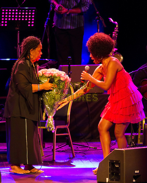 Cesaria Evora & Lura.Concert in Moscow, Russia..April 10th, 2011.on stage live gig performance performing music full length black top skirt singing red dress side profile flowers bouquet.CAP/PER/SB.©SB/PersonaStars/CapitalPictures