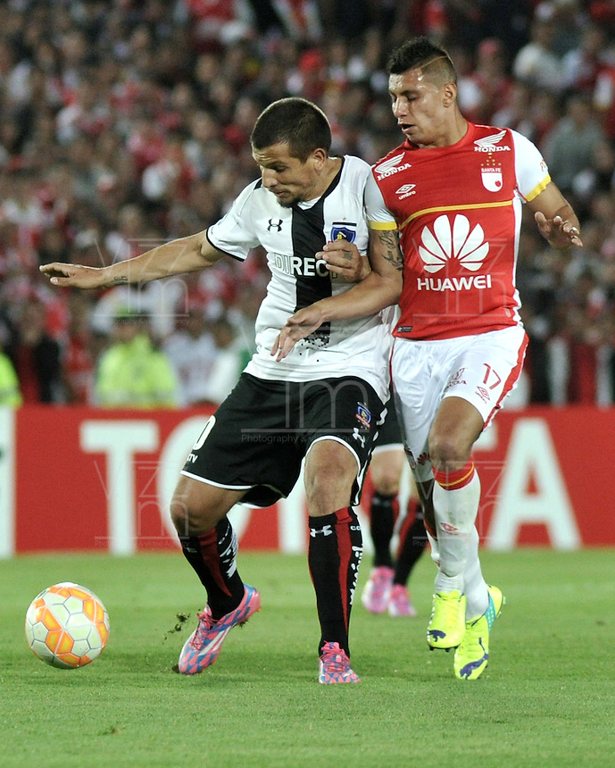 BOGOTA- COLOMBIA – 26-02-2015: Juan Roa (Der.) jugador del Independiente Santa Fe de Colombia, disputa el balón con Emiliano Vecchio (Izq.) jugador de Colo Colo de Chile, durante partido entre Independiente Santa Fe de Colombia y Colo Colo de Chile, por la segunda fase, grupo 1, de la Copa Bridgestone Libertadores en el estadio Nemesio Camacho El Campin, de la ciudad de Bogota. / Juan Roa (R) player of Independiente Santa Fe of Colombia, figths for the ball with Emiliano Vecchio (L) player of Colo Colo of Chile during a match between Independiente Santa Fe of Colombia and Colo Colo of Chile for the second phase, group 1, of the Copa Bridgestone Libertadores in the Nemesio Camacho El Campin in Bogota city. Photo: VizzorImage / Luis Ramirez / Staff.