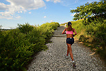 South Merrick, New York, USA - September 7, 2014 - Young woman, seen from back, jogs during a  late summer day with pleasant weather at Norman J Levy Park and Preserve marshland on Long Island, New York.