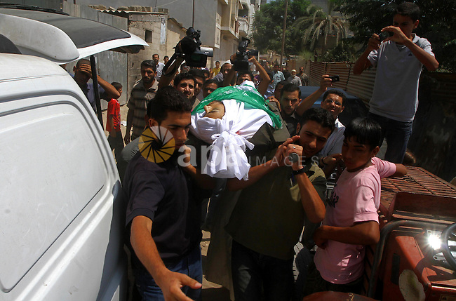 Palestinian mourners carry the body of Moussa Shtewi during his funeral in Gaza City on August 16, 2011 after he was killed and seven injured by overnight Israeli air strikes across the Gaza Strip, Palestinian medics said. The Israel Defence Forces (IDF) said the sites were targeted in response to the firing of a rocket from the Gaza Strip at the city of Beersheva. Photo by Ashraf Amra