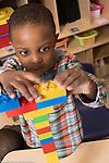 Education Preschool 3-4 year olds boy building tower with color plastic Duplo bricks