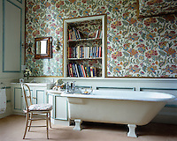 This comfortable bathroom has bookshelves lined in  fabric to match the wall covering