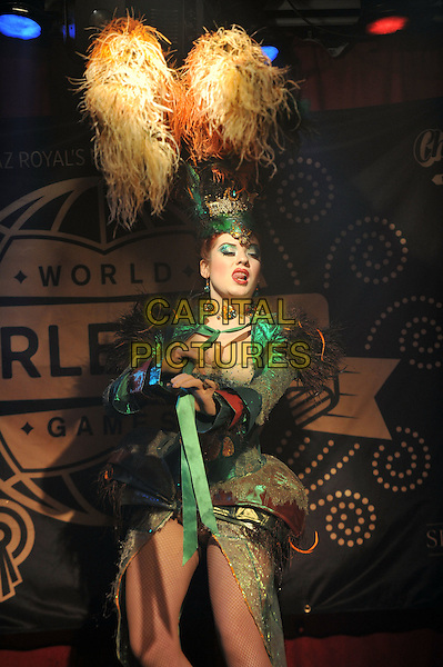World Burlesque Games Closing Night held at Madam JoJo's, Soho, London, England. .13th May 2012.on stage performance performing half length green dress yellow feathers hat.CAP/MAR.© Martin Harris/Capital Pictures.