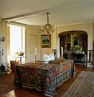 A large kilim rug covers the table in the hall