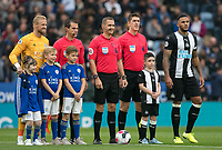 Goalkeeper Kasper Schmeichel of Leicester City, Jamaal Lascelles of Newcastle United, Referee Craig Pawson, officials Lee Betts and Ian Hussin with match day mascots during the Premier League match between Leicester City and Newcastle United at the King Power Stadium, Leicester, England on 29 September 2019. Photo by Andy Rowland.