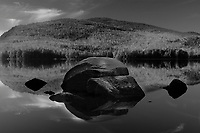 Boulders reflected and Pharoah Lake Mountain reflected in Pharoah Lake in the Adirondack Mountains in New York State