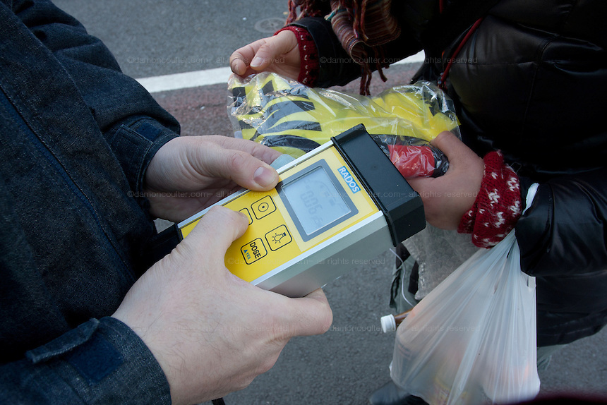 Protesters check radiation readings on a Geiger counter at an anti-nuclear power demo and occupy Tokyo protest outside the Ministry of the Economy, Trade and Industry (METI) in Tokyo, Japan. Friday 27th January 2012. The protest has been running from September 2011 and was scheduled for forcible eviction by police at 5pm on January 27th as the camp had been declared a fire risk by Minister Yukio Edano, with around 500 supporters and protesters turning up to resist the eviction however the camp was still in place the night of the 27th.