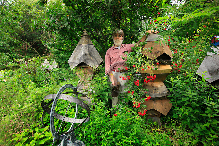 Ron Breland poses in front of his experimental hives. Former publicity photographer, Ron left New York City twenty years ago. Today, he teaches organic gardening and apiculture at the private Rockland Country Day School in Congers, thirteen or so miles out of Manhattan.