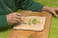 Kinder basteln Blattkacheln aus Salzteig, Junge malt den Abdruck von einem Eichenblatt auf dem Salzteig an