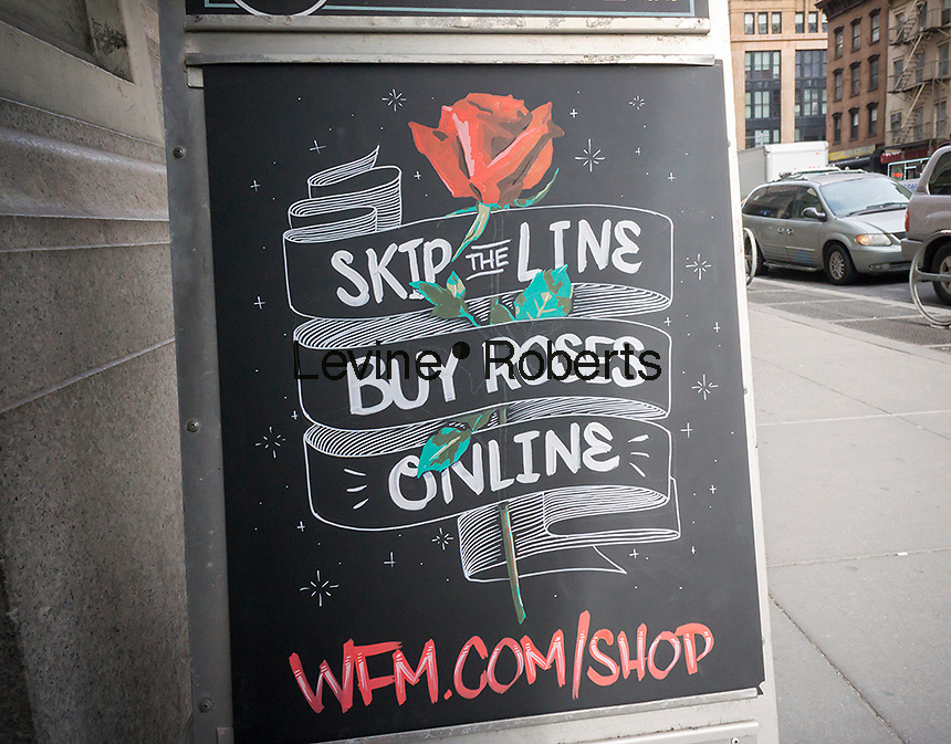 A sign outside of the Whole Foods Market in Chelsea in New York promotes their website sales of Valentine's Day flowers, seen on Friday, February 12, 2016. The National Retail federation estimates 55% of all Americans celebrate Valentine's Day spending an average of $146.84. (© Richard B. Levine)