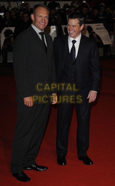 "FRANCOIS PINEAAR & MATT DAMON.Attending the ""Invictus'"" UK Film Premiere at the Odeon West End cinema, Leicester Square, London, England, January 31st, 2010. .arrivals full length grey gray tie black suit pinstripe shoes navy blue waistcoat smiling funny laughing .CAP/CAN.©Can Nguyen/Capital Pictures"