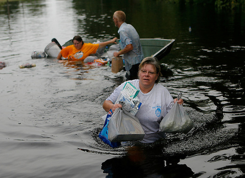Cindy Pomeroy (foreground) carries supplies to her boat after the boat of Jennifer Fraley (yellow shirt) and Dean Oxley (in boat with Jennifer) capsized. Fraley and Oxley were being towed by the boat of Cindy and Chuck Pomeroy when the wake of the front boat flooded the boat being towed. Most of the supplies were saved. The River Plantation subdivision in Walker County near Trinity suffered flooding to many of the homes that weren't on pilings. Residents used boats to ferry supplies for themselves and their neighbors. (yellow shirt), (Wednesday, July 18, 2007,  Steve Campbell / Chronicle)