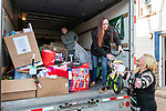 WOLCOTT, CT. 23 December 2018-122318 - Joanne Soden, the founder of the group Stocking Stuffers who has been giving gifts on Christmas for 10 years, right, passes the torch to her daughter so to speak by giving her a bicycle to load in the truck as her grandson Stephen Tedd organizes inside at the Grange in Wolcott on Sunday. The gifts will be distributed on Christmas Day with help from the Waterbury Fire and Police departments to families less fortunate for the holidays. Bill Shettle Republican-American