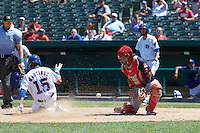 Peoria Chiefs catcher Jose Godoy (27) waits for a throw as Eddy Martinez (15) slides home safely with the game winning run as umpire Andy Stukel looks on during the first game of a doubleheader against the South Bend Cubs on July 25, 2016 at Four Winds Field in South Bend, Indiana.  South Bend defeated Peoria 9-8.  (Mike Janes/Four Seam Images)