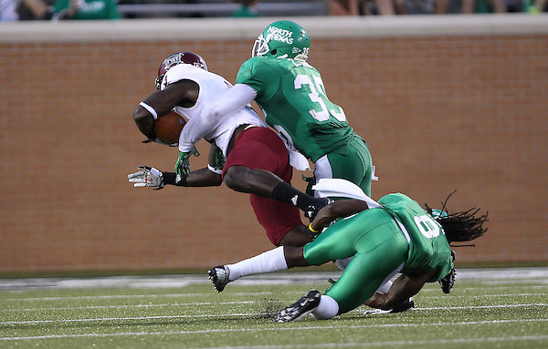 Denton, TX - SEPTEMBER 22: Defensive back Marcus Trice #8 of the North Texas Mean Green and linebacker Zachary Orr #35 tackle wide receiver Eric Thomas #3 of the Troy Trojans at University of North Texas Apogee Stadium in Denton on September 22, 2012 in Denton, Texas. (Photo by Rick Yeatts)