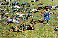 A Colombian baby girl running across the army gear after the demobilization ceremony of the AUC paramilitary forces, Meta Department, Colombia, 10 April 2006.