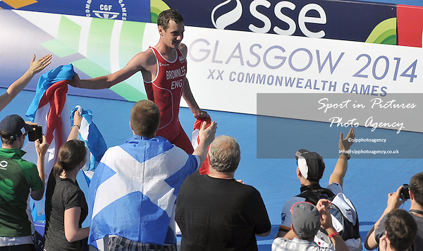 Alistair Brownlee (ENG) collects a Yorkshire flag from the crowd. Men's Triathlon at the 2014 Commonwealth Games. <br /> PHOTO: Mandatory by-line: Garry Bowden/SIPPA/Pinnacle - Tel: +44(0)1363 881025 - Mobile:0797 1270 681 - VAT Reg No: 183700120 - 240714 - Glasgow 2014 Commonwealth Games - Strathclyde County Park, Glasgow, Scotland, UK