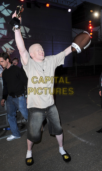 DARNELL SWALLOW .Housemates enter the Big Brother House for Big Brother 9, Borehamwood, England. .June 5th, 2008.arrivals full length american football brown t-shirt denim jean shorts slippers socks arms in air albino trophy .CAP/BEL.©Tom Belcher/Capital Pictures.