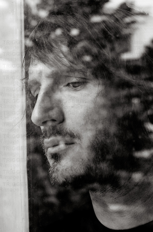 young bearded man looking out of the window
