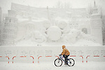 A man cycles in heavy snow past an ice sculpture during the snow and ice festival in Sapporo City, northern Japan. About 2 million people visit the city to see the hundreds of hand-crafted snow and ice sculptures that have graced the Sapporo Snow Festival since its inception in 1950.