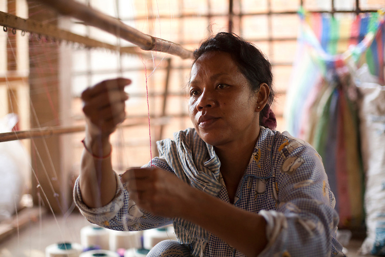 A women works in a small village textile factory outside of Phnom Penh, Cambodia. <br /> <br /> Photos &copy; Dennis Drenner 2013.