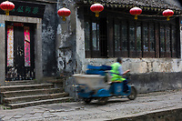 Suzhou, Jiangsu, China.  Three-wheeled Goods Transporter Speeds through Tongli Ancient Town near Suzhou.