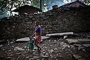 An old woman walks with a little girl in Village Sirisgura in Bastar district of Chattisgarh, India. The local villagers are protesting against Tata and the local government for forcibly acquiring their village. Photo: Sanjit Das/Panos for The Times