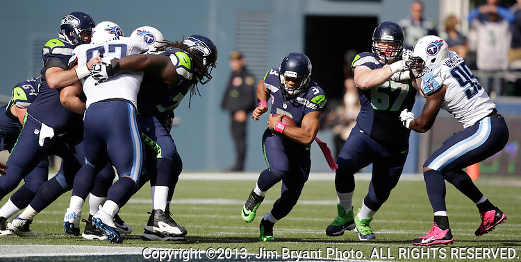 Seattle Seahawks quarterback Russell Wilson scrambles against the Tennessee Titians at CenturyLink Field in Seattle, Washington on  October 13, 2013. The Seattle Seahawks beat the Titians  20-13.   ©2013. Jim Bryant Photo. All Rights Reserved.