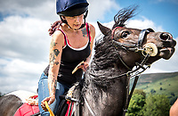 A local tattooed rider wins a prize at the race and clips a winner's ribbon onto her horse.