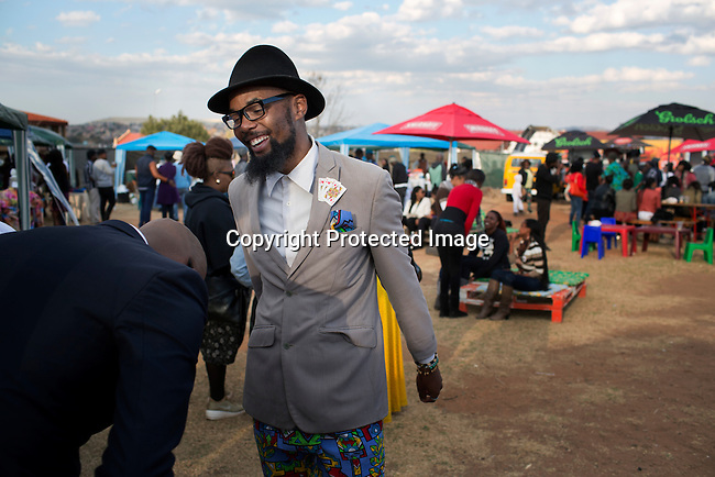 SOWETO, SOUTH AFRICA JULY 6: Smarteez designer Lethabo Tsatsinyane (l) chats to friends at an outdoor market on July 6, 2014 in Orlando West section of Soweto, South Africa. Soweto today is a mix of old housing and newly constructed townhouses. A new hungry black middle-class is growing steadily. Many residents work in Johannesburg but the last years many shopping malls have been built, and people are starting to spend their money in Soweto. (Photo by: Per-Anders Pettersson)