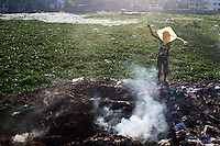A Bangladeshi child plays with a kite, as smoke emits from burning waste on the bank of the river Buriganga in Dhaka, Bangladesh.