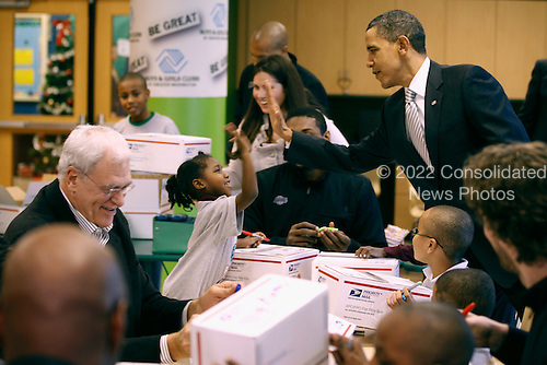 United States President Barack Obama (R) gives a girl a high-five while helping Los Angeles Lakers head coach Phil Jackson (L) and other team members and children volunteers fill care packages during a NBA Cares service event at the Boys and Girls Club at THEARC,   December 13, 2010 in Washington, DC. Bryant and all the members of the 2010 NBA Championship Lakers team volunteered on projects at the club before being honored by the president for their victory.  .Credit: Chip Somodevilla - Pool via CNP