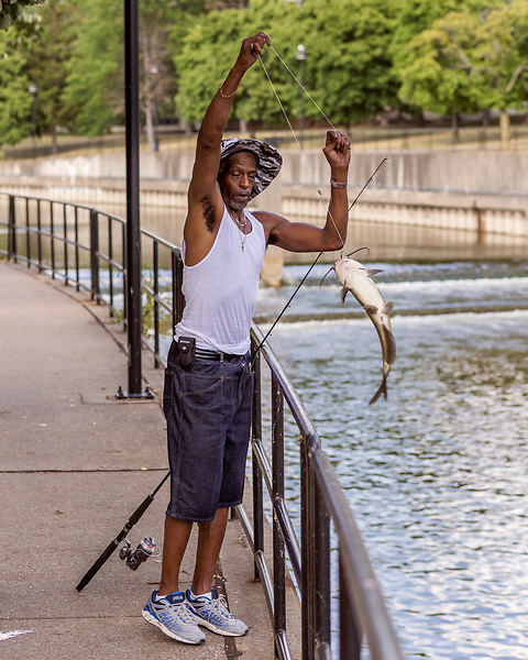August 5, 2016. Flint, Michigan.<br />  DeAidre Avant, a truck driver and lifelong Flint resident, pulls a large catfish from the downtown section of the river. <br />  In April 2014, the city of Flint switched its water source from the Detroit Water and Sewerage Department to using the Flint River in an effort to save money. When the switch occurred, the city failed to have corrosion control treatment in place for the new water. This brought about a leaching of lead from pipes into the water, increasing the lead content in the drinking water to levels far above legal limits. After independent sources brought this to light, the city admitted the water was unsafe and legal battles have ensued between resident and the local and state governments.