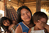 Aldeia Baú, Para State, Brazil. Kayapo woman with her two daughters sitting in a hammock