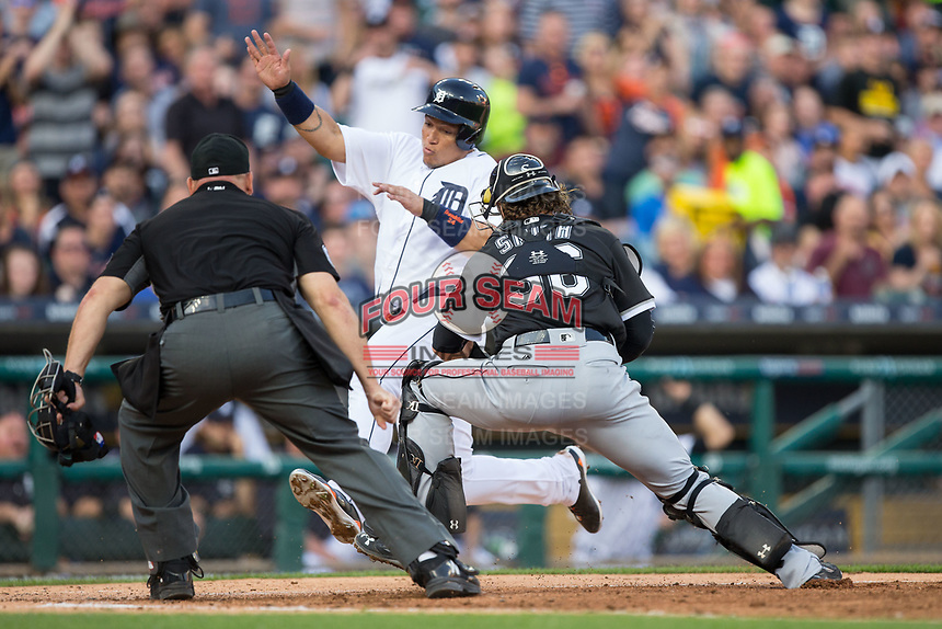 Chicago White Sox catcher Kevan Smith (36) prepares to apply a tag to Miguel Cabrera (24) of the Detroit Tigers as home plate umpire Mark Carlson looks on at Comerica Park on June 2, 2017 in Detroit, Michigan.  The Tigers defeated the White Sox 15-5.  (Brian Westerholt/Four Seam Images)