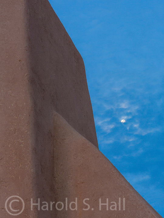 The moon is setting behind the San Francisco de Asis church in Ranchos de Taos in New Mexico.