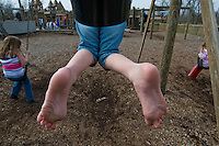 A young girl's feet dangle in the air as she reaches the top of her arc while playing on a swing set in a park.   Photo Copyright Gary Gardiner. Not be used without written permission detailing exact usage.
