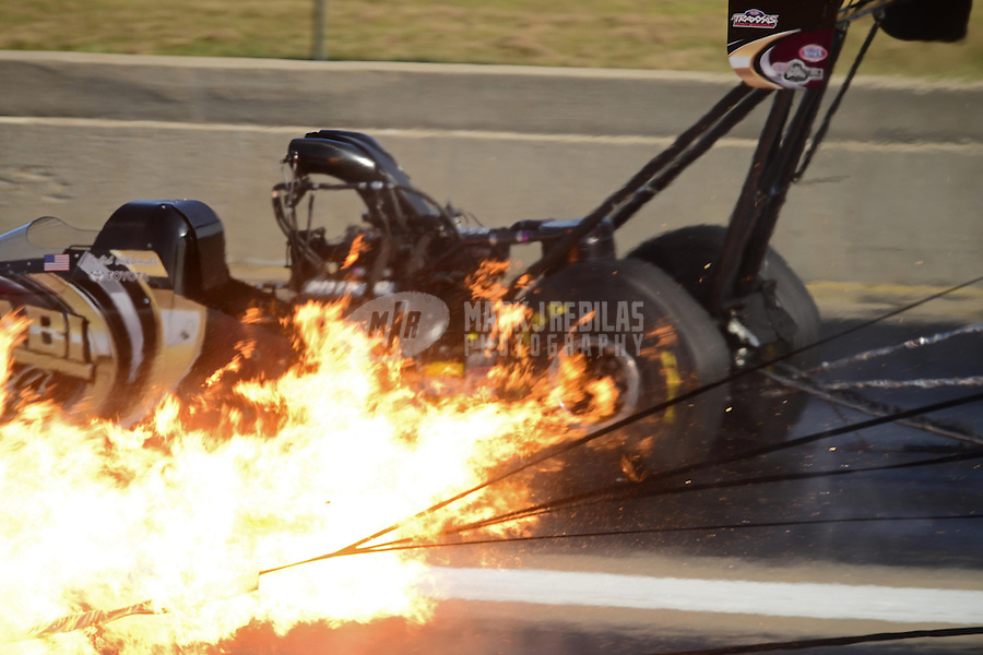 Sept. 22, 2012; Ennis, TX, USA: NHRA top fuel dragster driver Khalid Albalooshi (far lane) races alongside a fire from the engine exploding of Doug Kalitta during qualifying for the Fall Nationals at the Texas Motorplex. Mandatory Credit: Mark J. Rebilas-