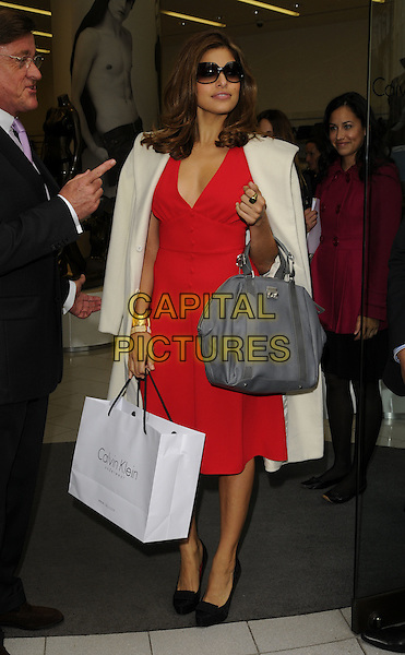 EVA MENDES.Arriving for a personal appearance at the Calvin Klein store, Regent St., London, England..Ocotber 14th, 2008.mendez full length red dress white coat grey gray bag sunglasses shades black shoes goody.CAP/CAN.©Can Nguyen/Capital Pictures.
